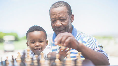 Man plays chess with young child